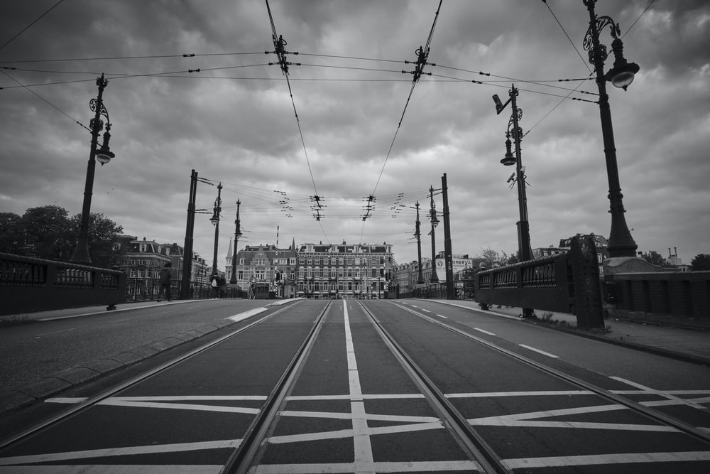 grayscale photography of road towards building