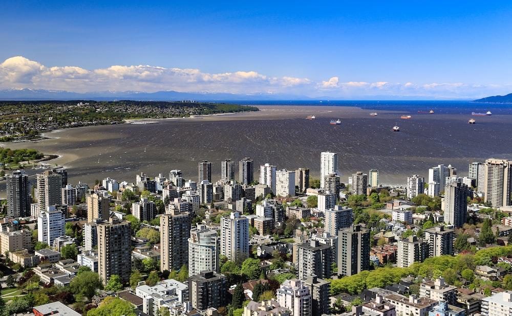 aerial photo of buildings facing ocean under blue sky