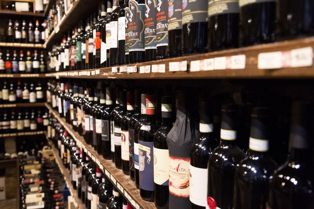 assorted wine bottle lot displaying on rack