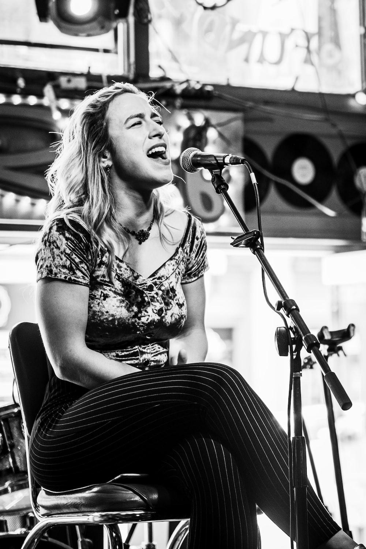 greyscale photo of woman singing inside studio