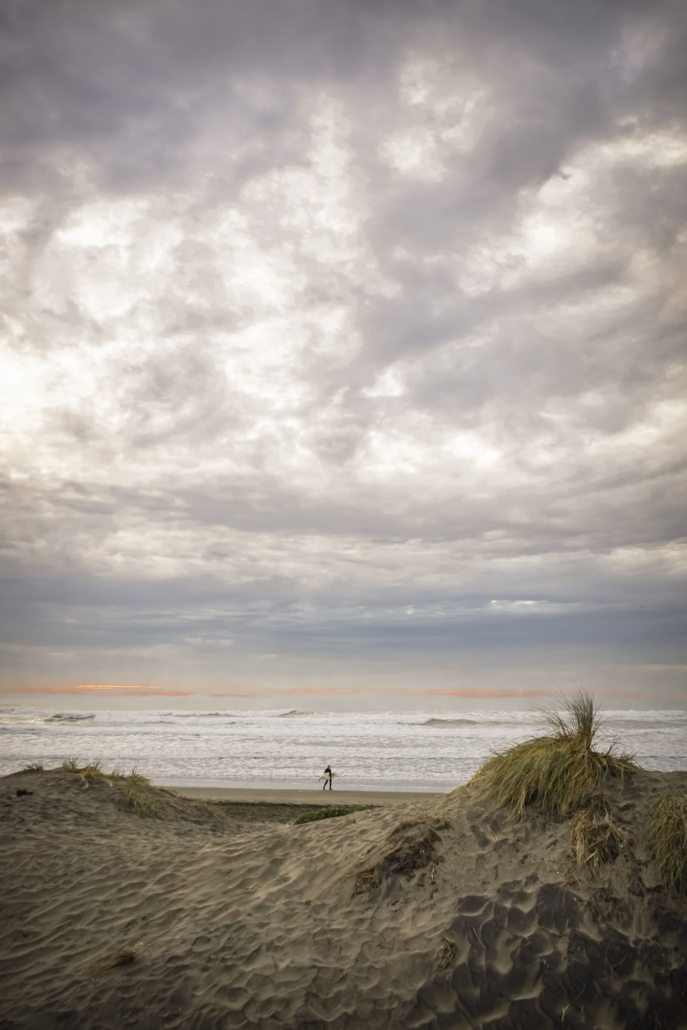person in shore under gray clouds