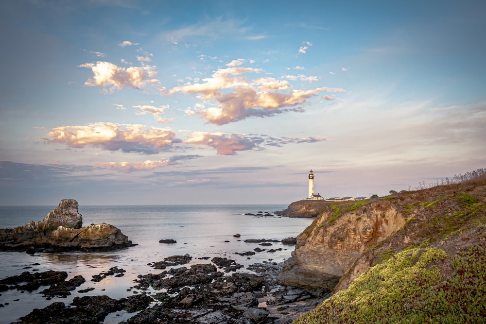 lighthouse on cliff under blue skies