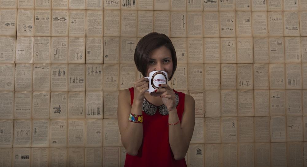 woman in red tank dress holding white mug