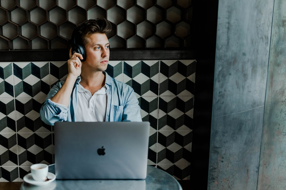man sitting in front of silver MacBook