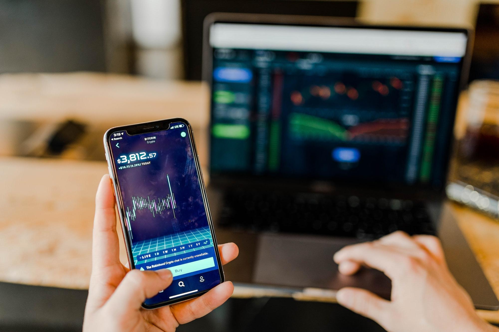 Imagem mostra um tela de investimentos ao fundo e uma mão segurando um telefone com outra tela de investimentos em primeiro plano.