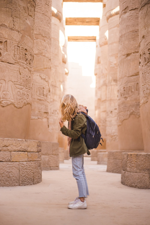 woman in brown jacket standing near brown concrete pillars
