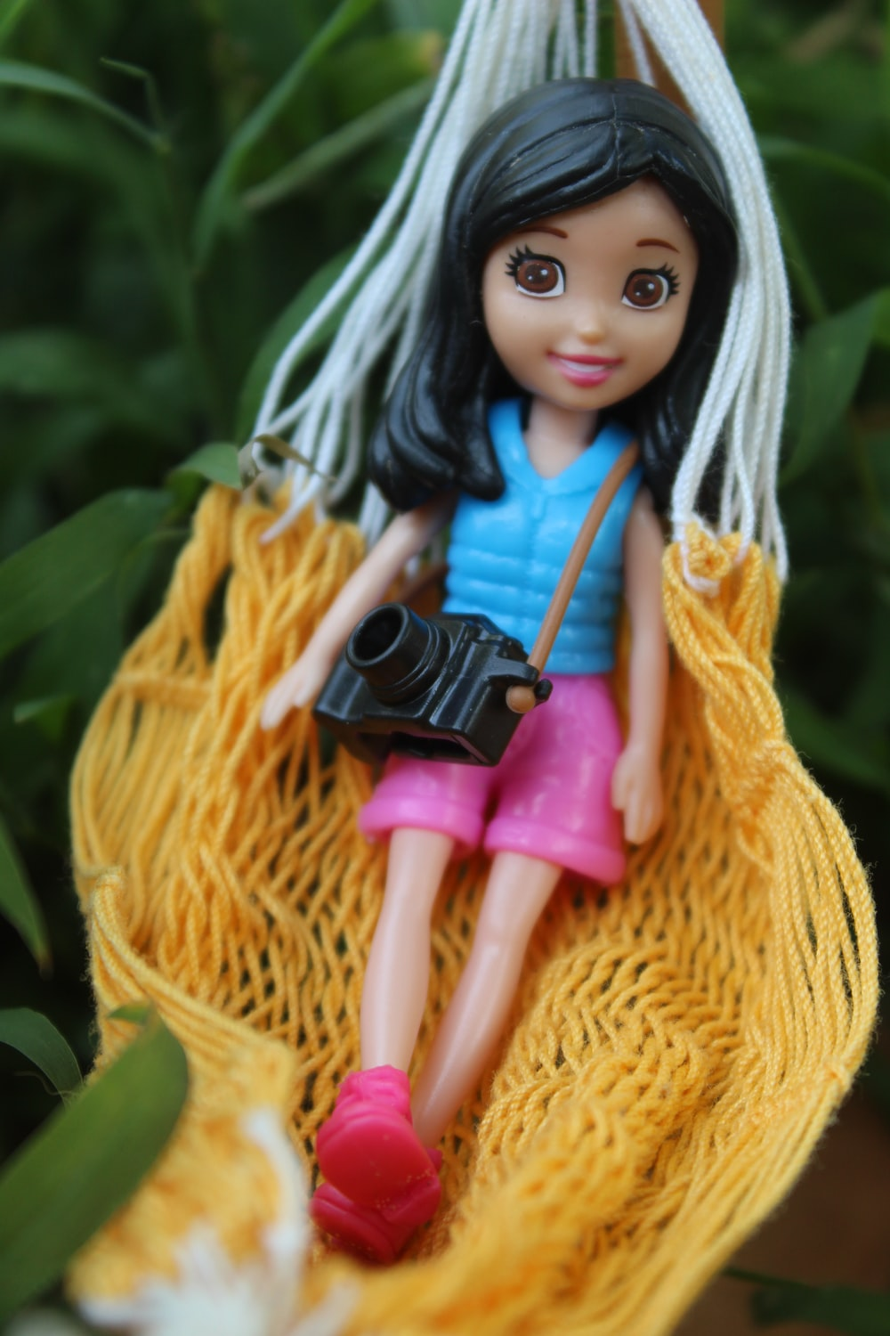 girl wearing blue tank top and shorts doll on hammock