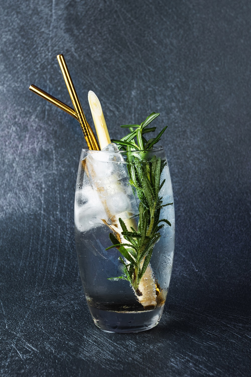 Rosemary herb inside clear glass with water and yellow straw