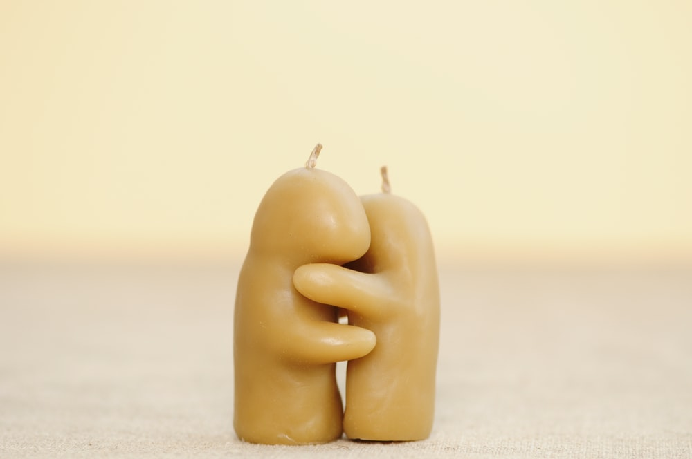 two beige hugging candles on white surface