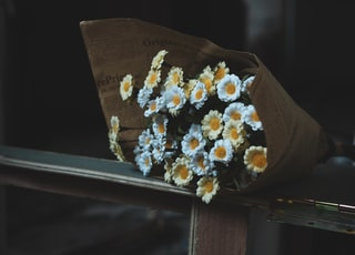 yellow and white flowers bouquet on brown wooden bench