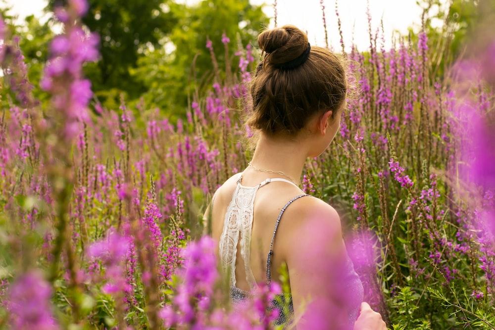 Purple island - woman standing on pin flowers field