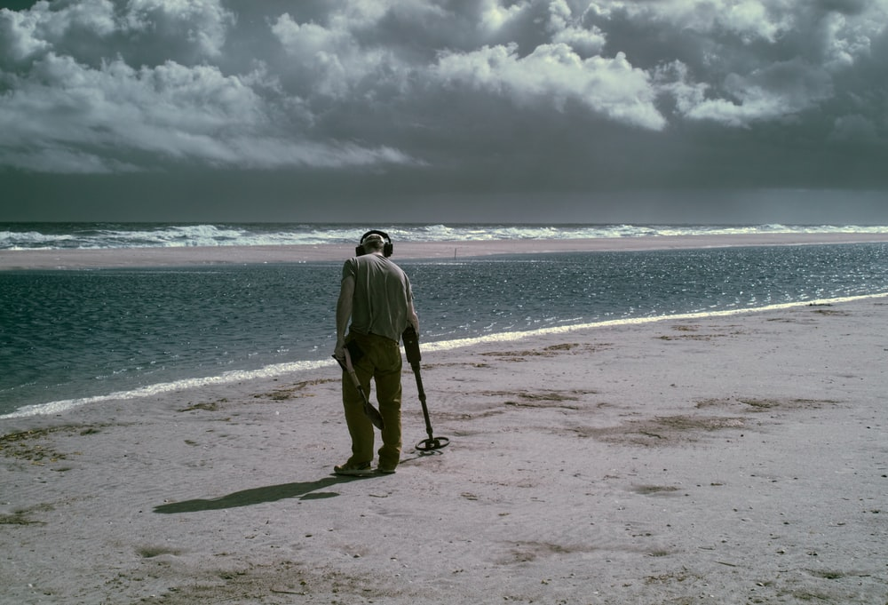 man using metal detector at the shore during day