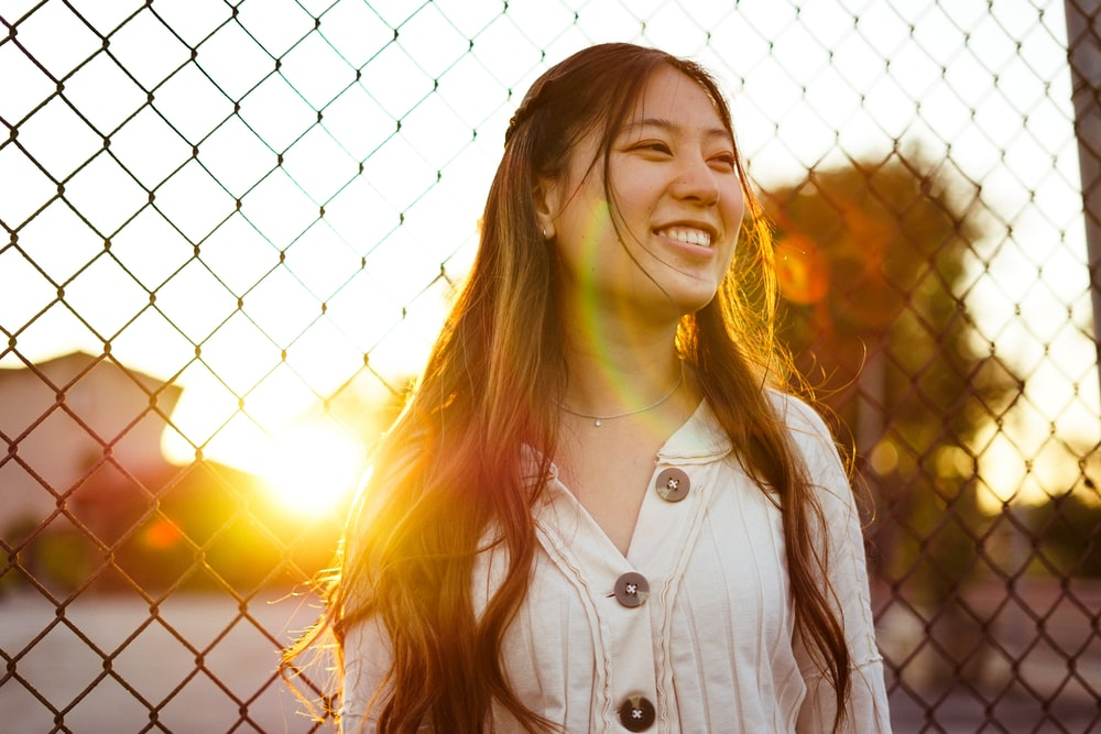woman smiling in front of chain link fence during golden hour