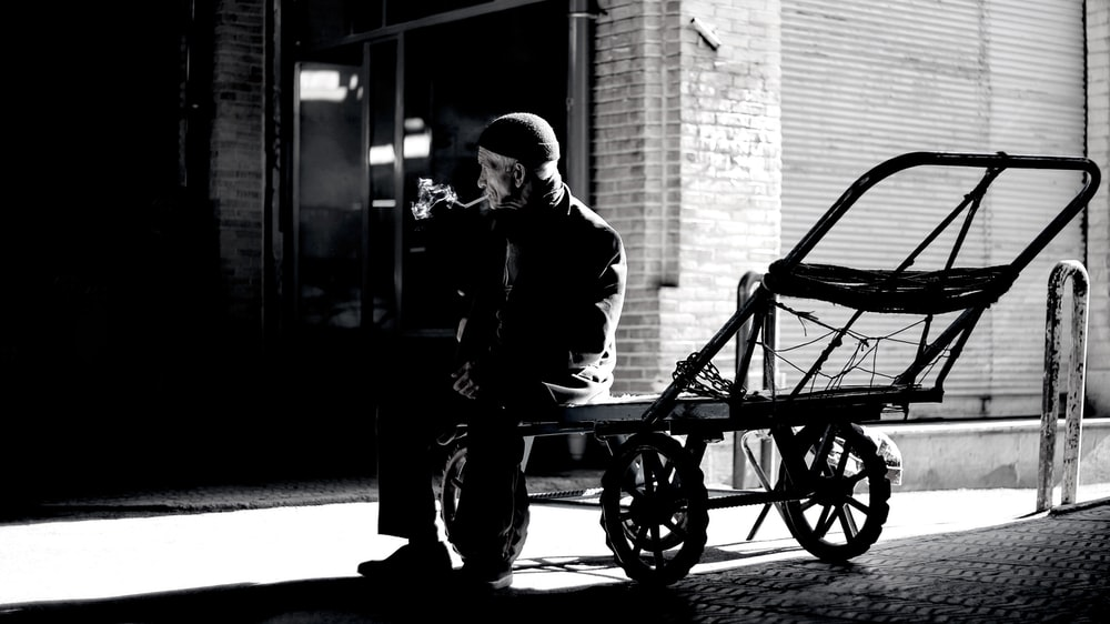 grayscale photography of person sitting on trailer