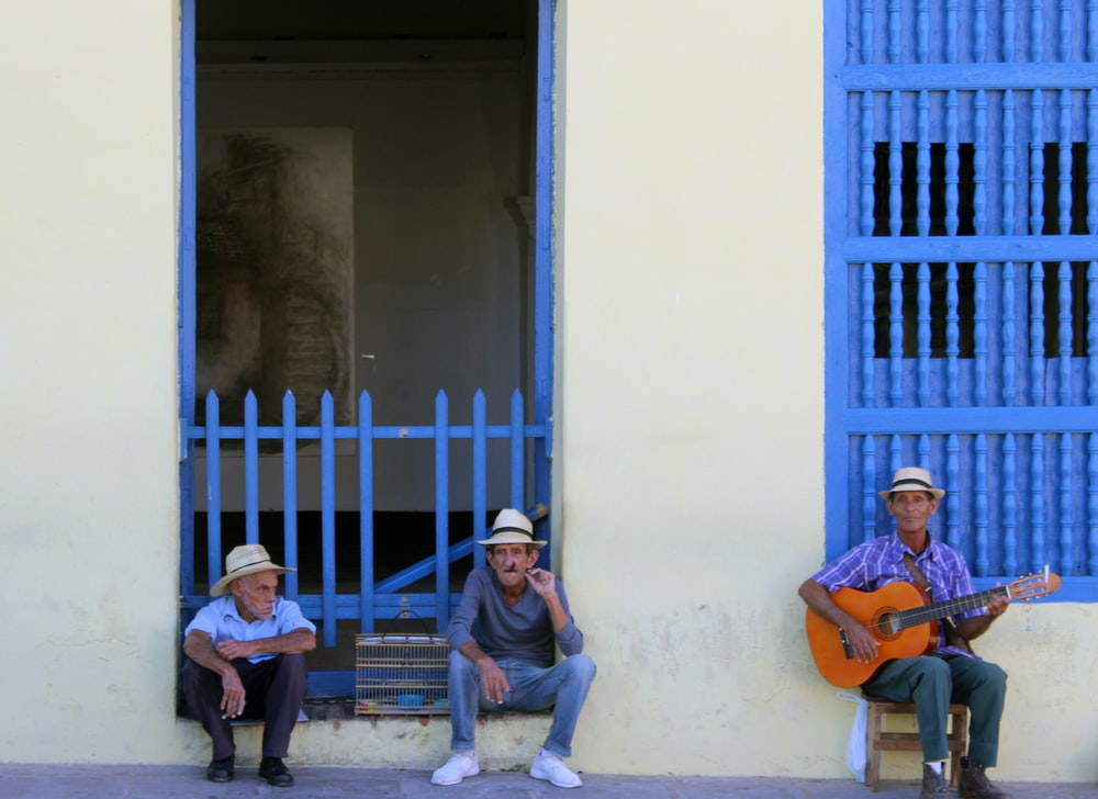 three men sitting near white building