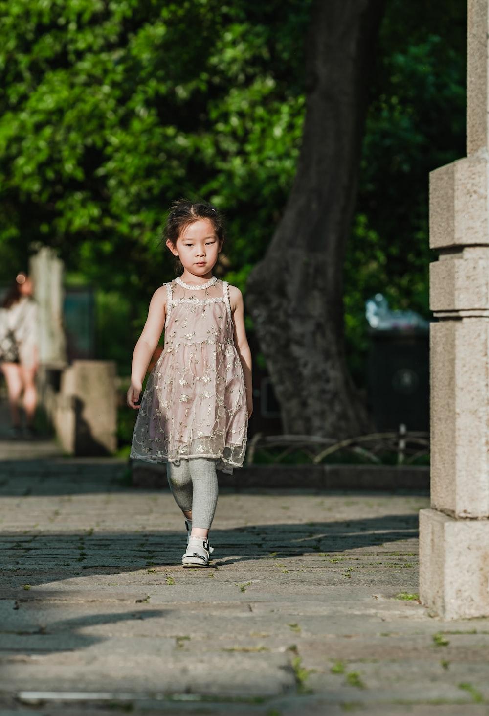 girl walking on concrete pathway near tree