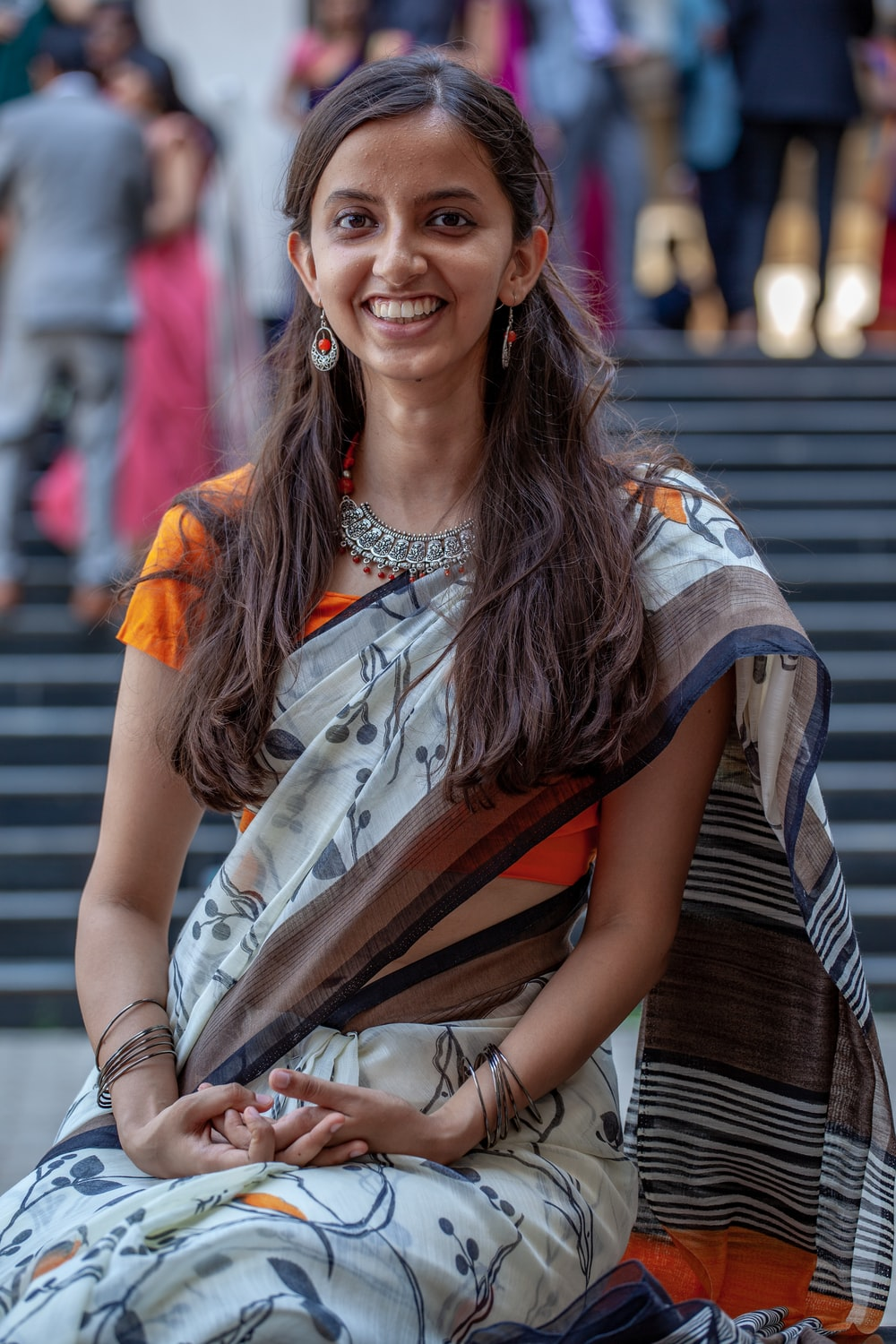 smiling woman in orange and white saree sitting on chair