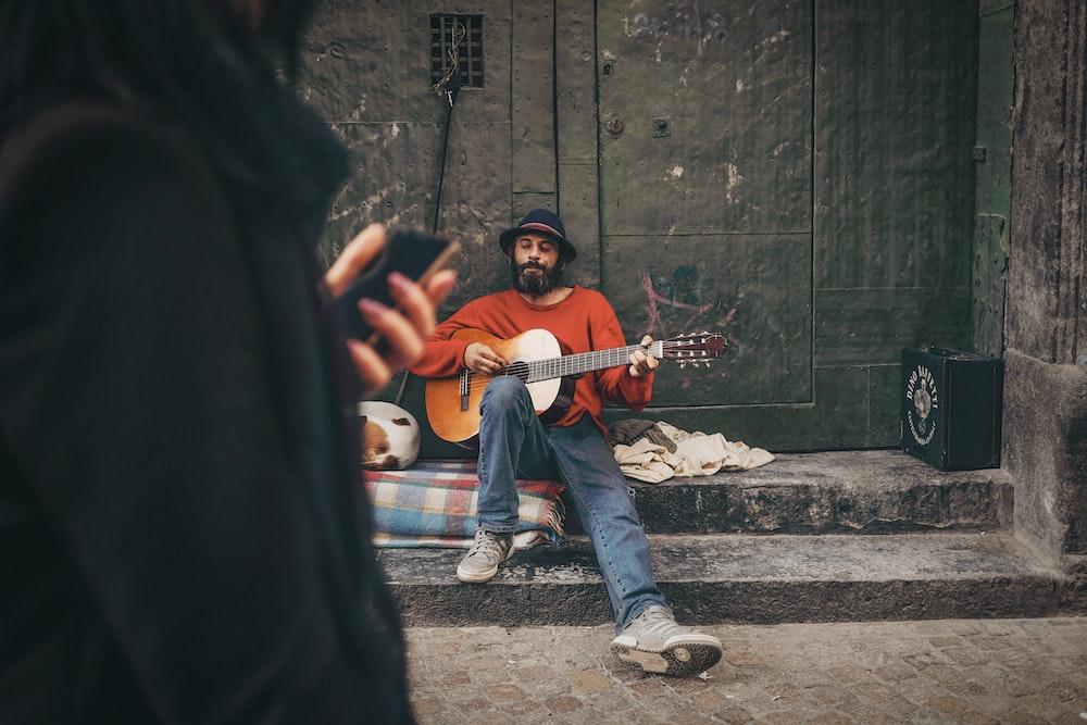 man holding orange guitar