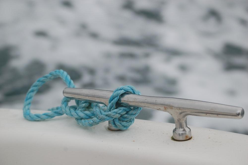 teal rope tied on gray metal part