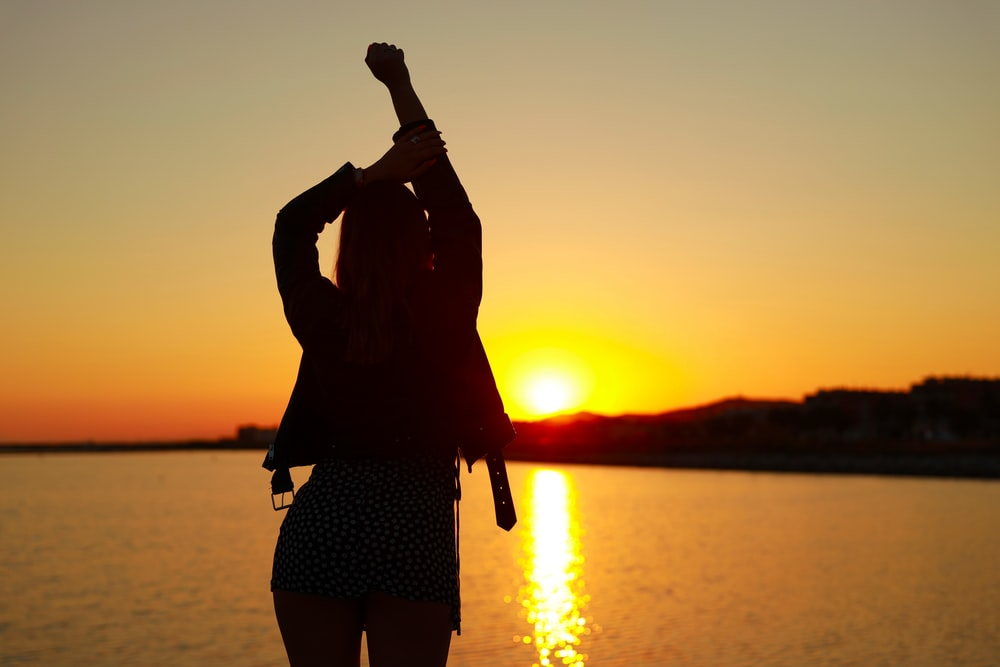 silhouette of woman standing on shore