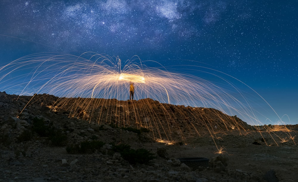 man holding fireworks on top of hill