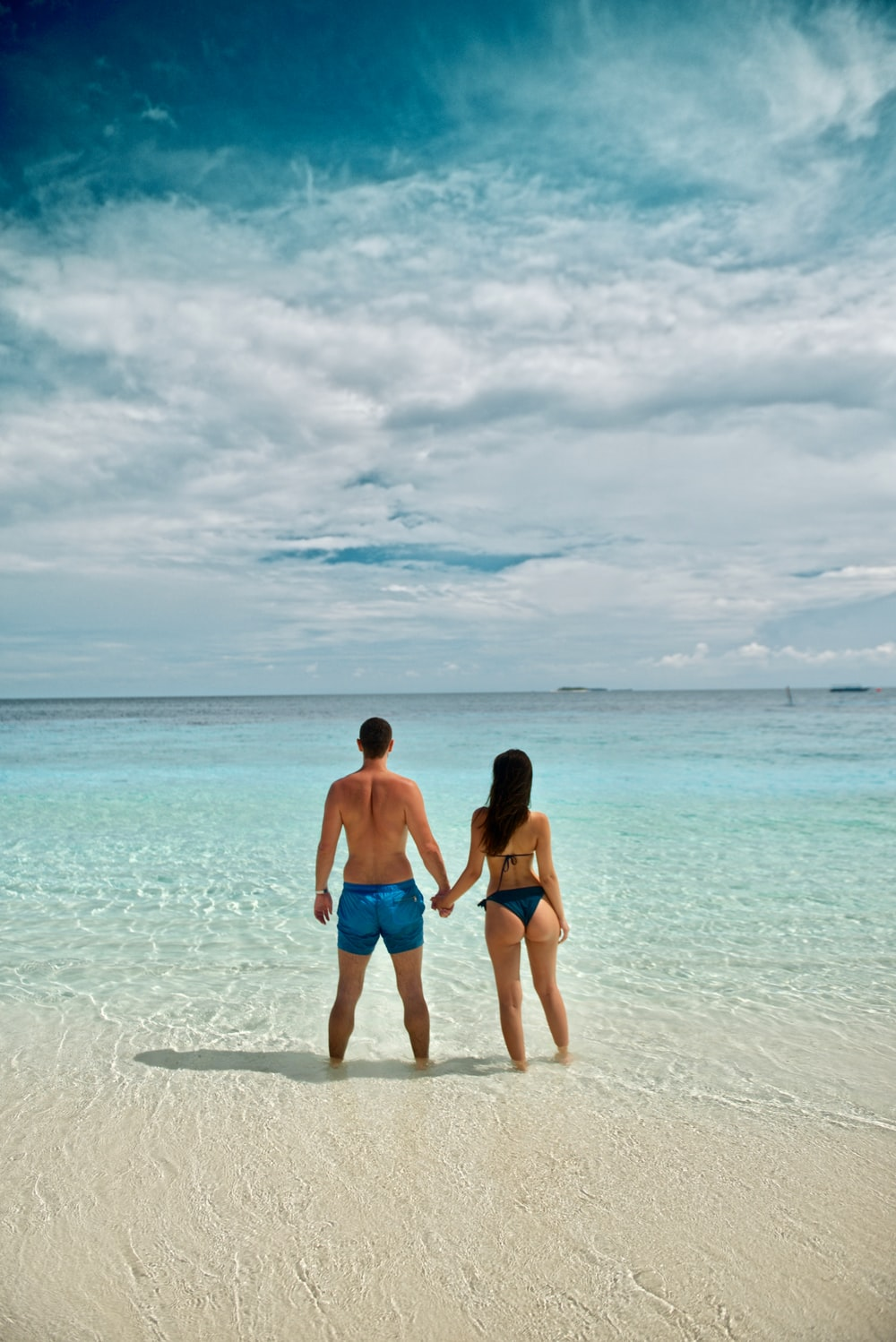 woman holding man's hand standing on shore