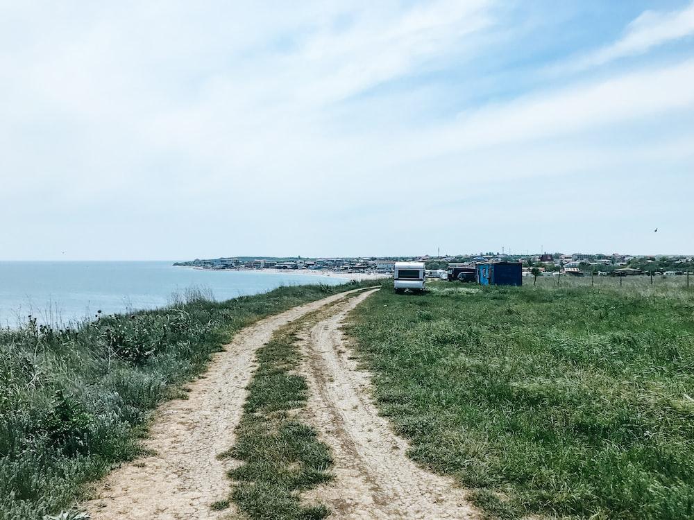white travel trailer beside body of water