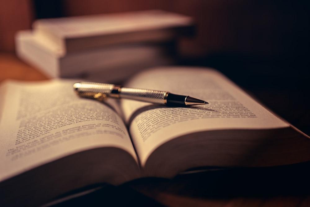 gray click pen on open book