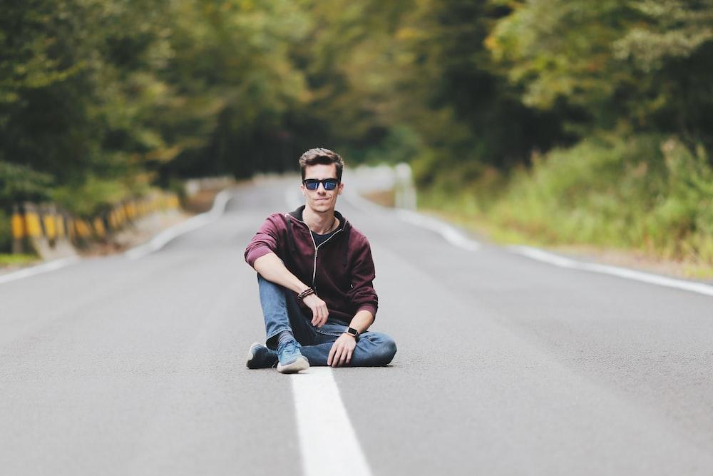 man sitting on empty road between trees