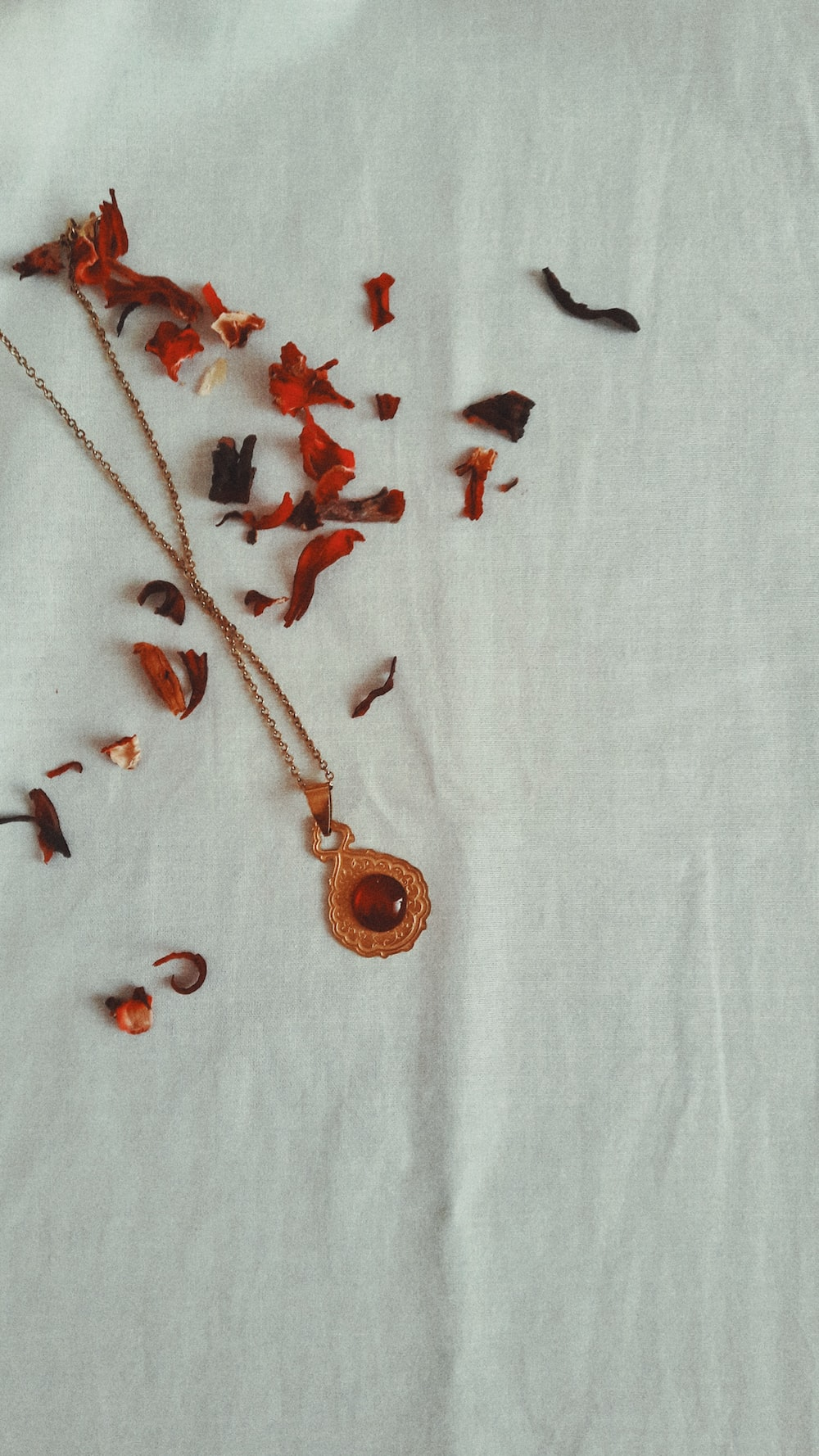 red gemstone pendant necklace on white textile