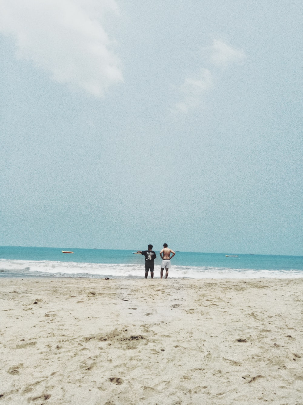 two men standing next to each other on shore