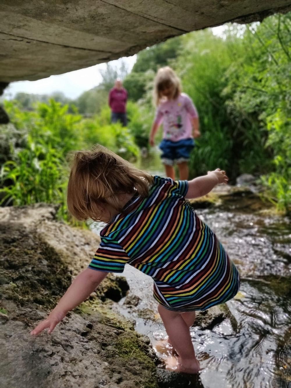 two children walking on water stream