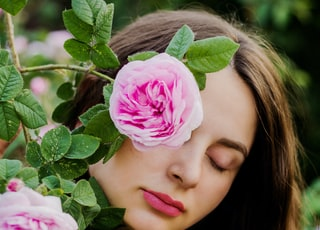 woman hiding behind pink petaled flower during daytime