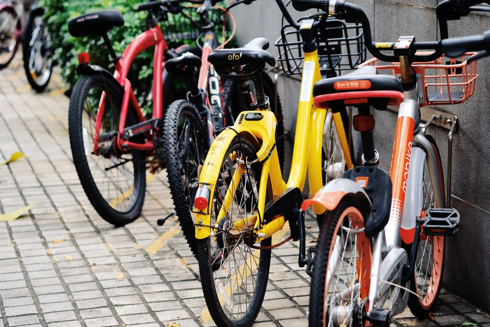 four assorted-color bicycles parked beside gray wall