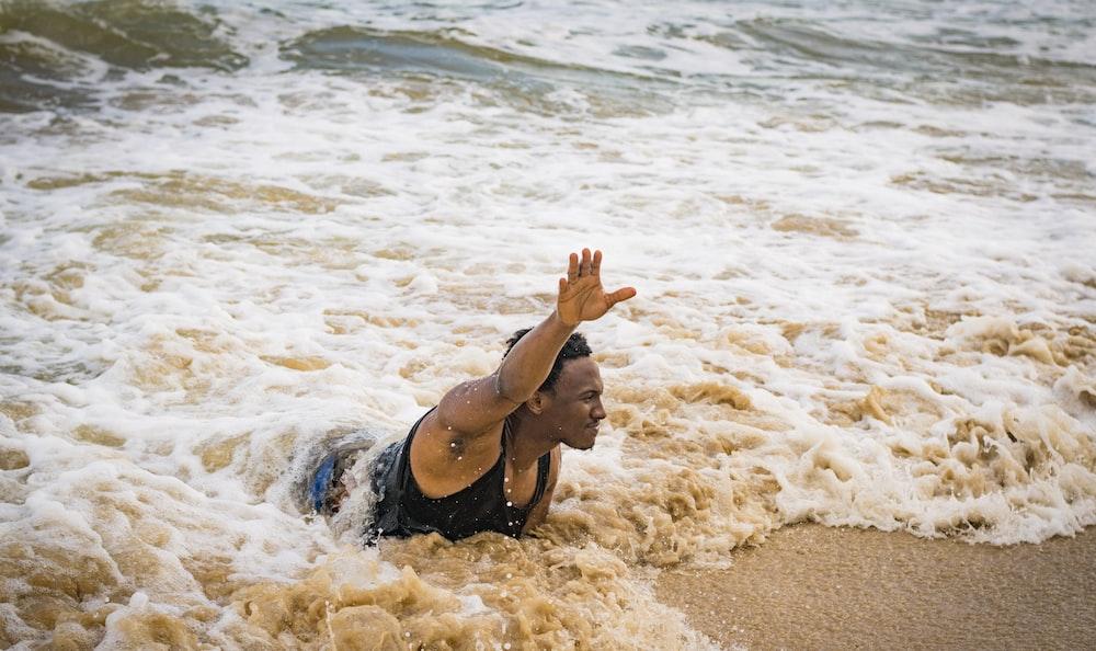 man swimming on beach during daytime