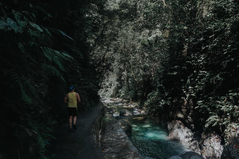 man walking beside river near mountain during daytime
