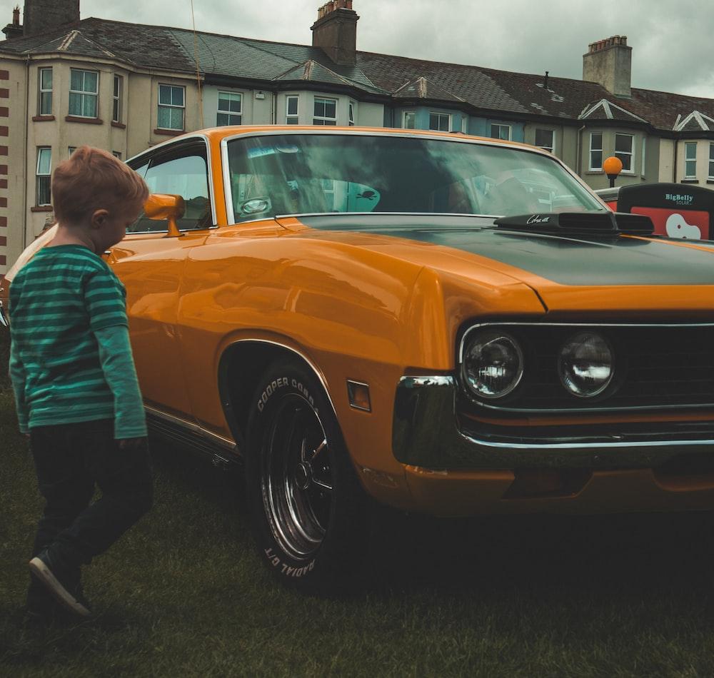 boy beside orange car