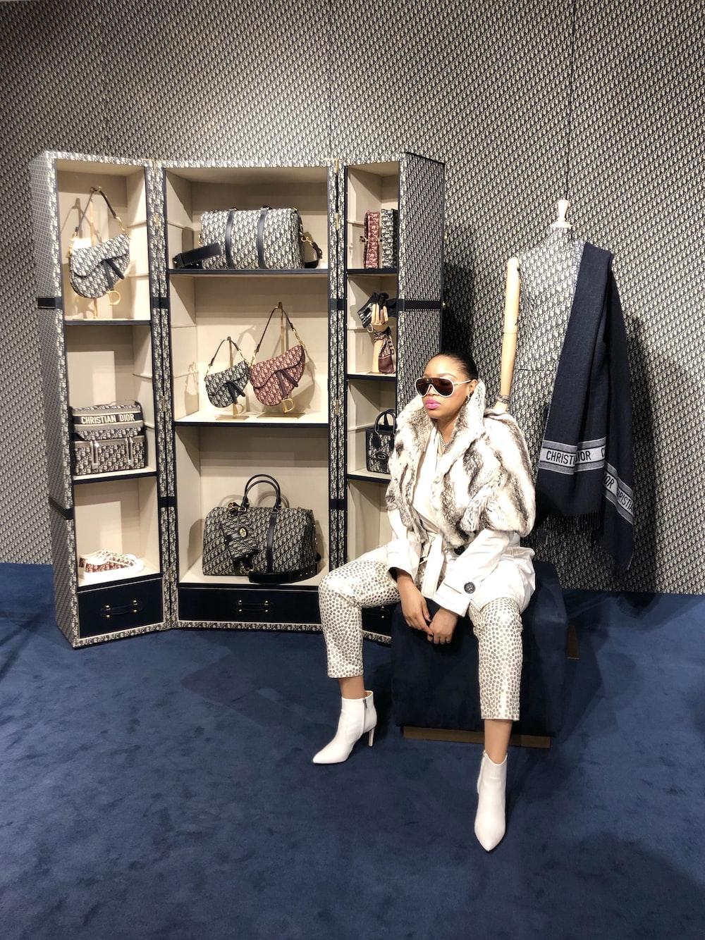 woman sitting on chair near open cabinet