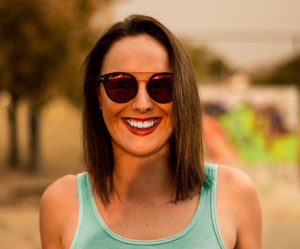 woman in green tank top wearing sunglasses and smiling
