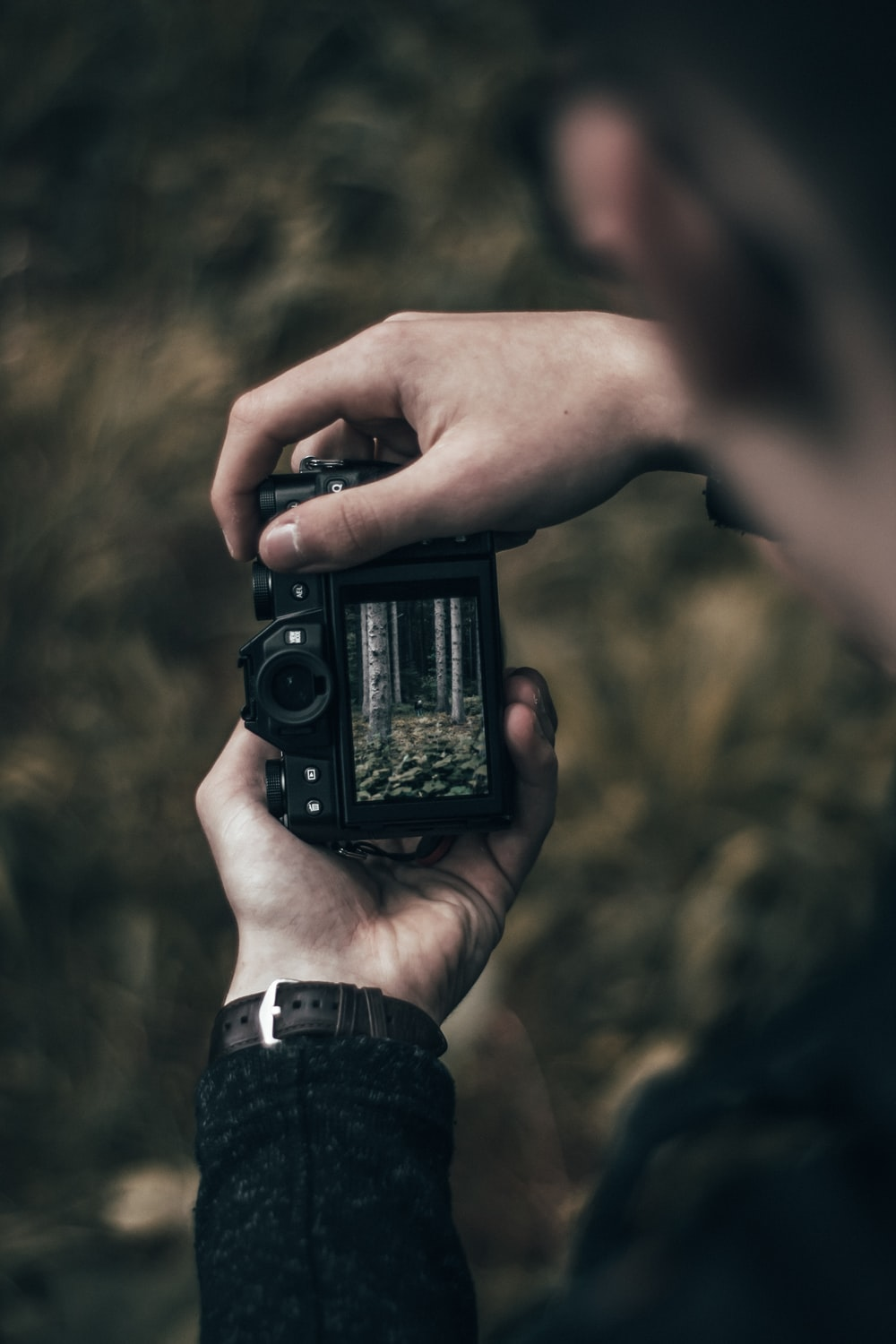 selective focus photography of person holding black camera