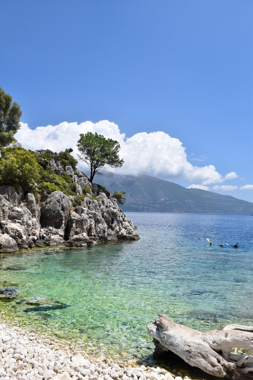 landscape photography of beach near rock mountain