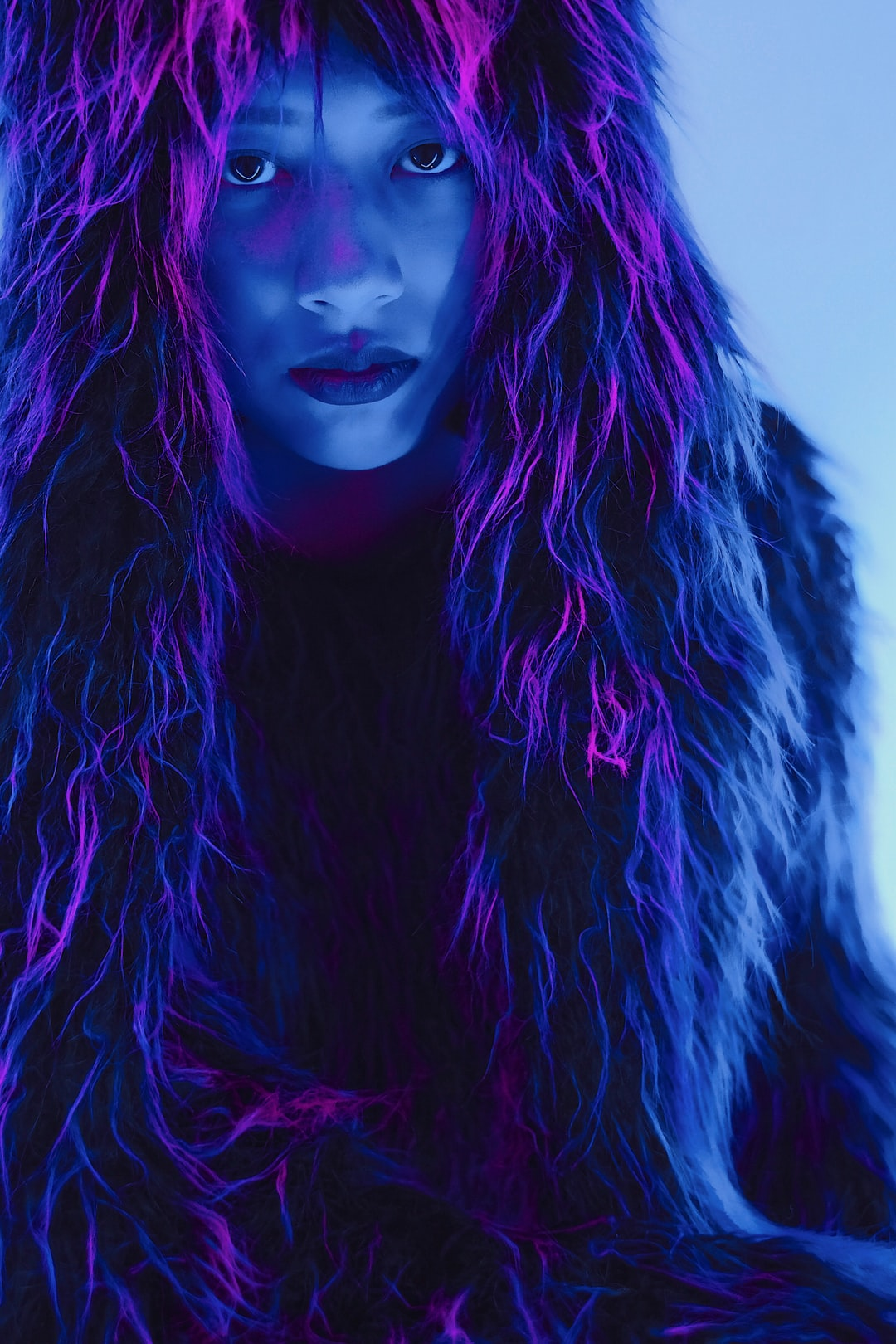 An image of a serious-faced woman draped in furs, lit in futuristic purples and blues.