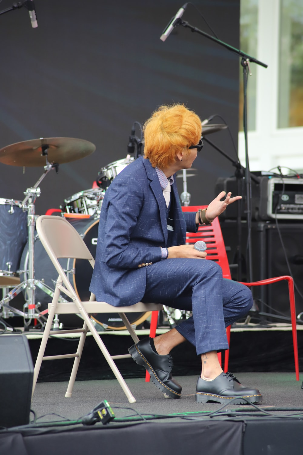 man wearing suit sitting on folding chair while holding microphone