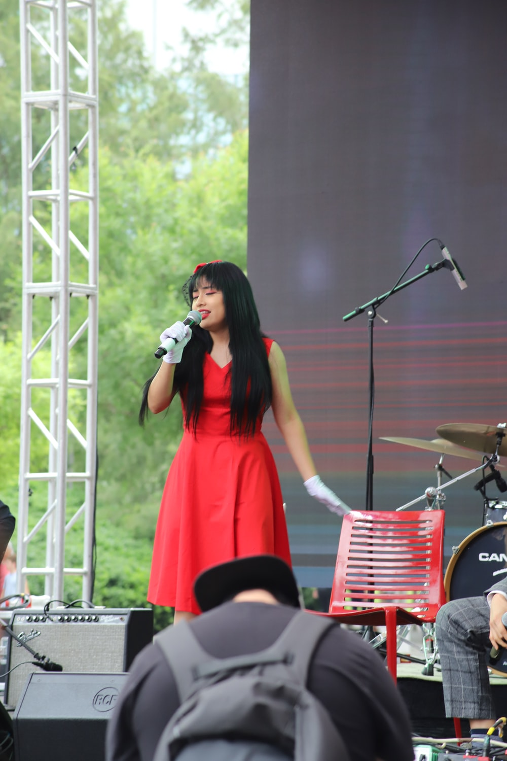 photography of woman singing near stage during daytime