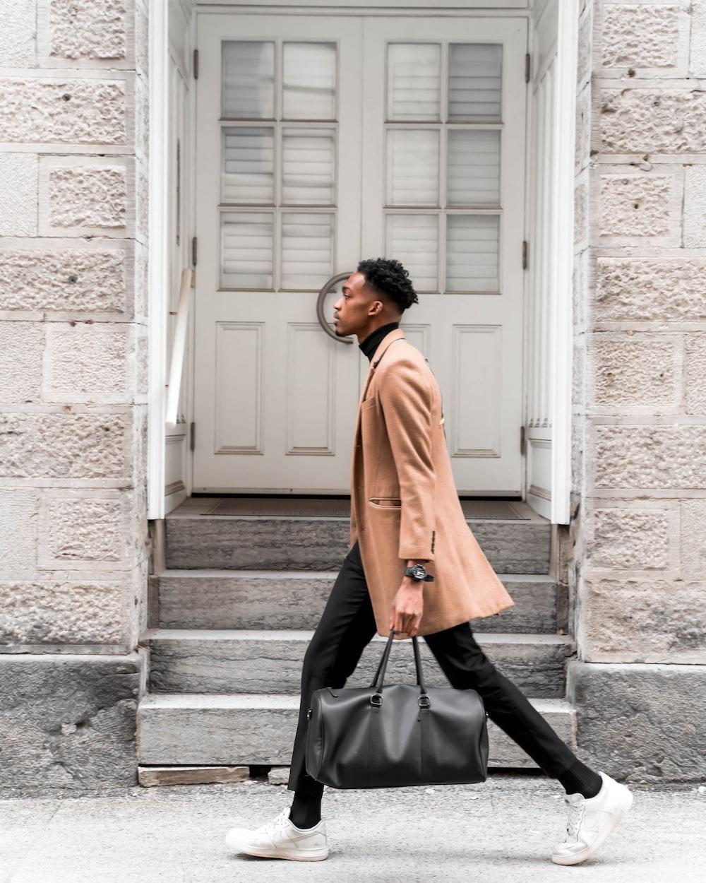 man walking on road while holding bag during daytime