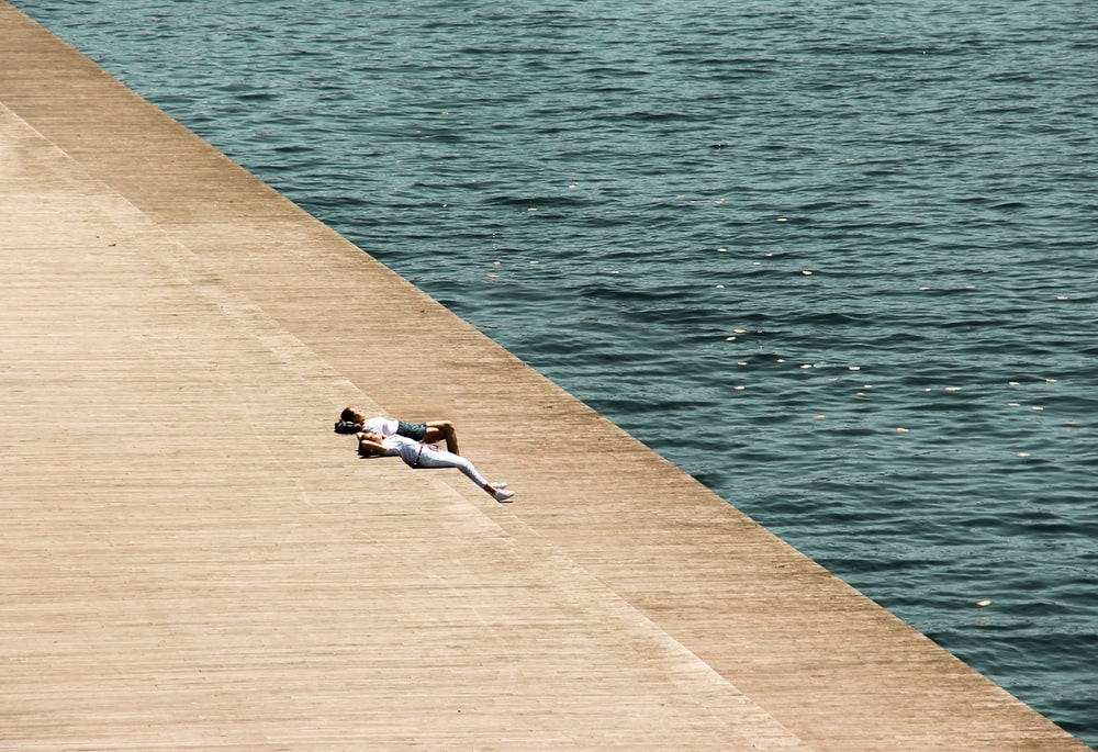 person lying on ground near body of water