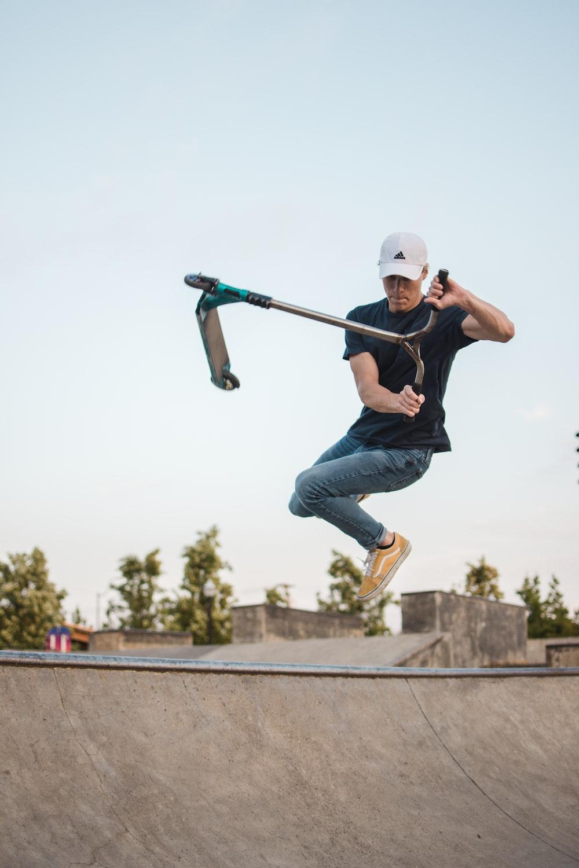 man wearing black crew-neck shirt doing trick on kick scooter