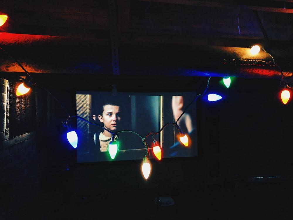 flat screen television near string lights