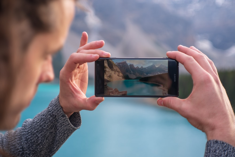 man capturing body of water and mountains from his phone