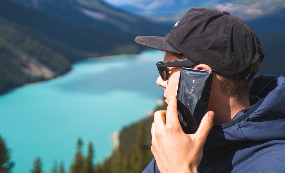 man near outdoor holding smartphone while starring on lake during daytime